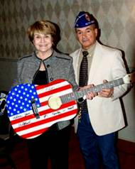 Louise Slaughter and Gene Simes display Willie Nelson and Charlie Daniels signature guitar.